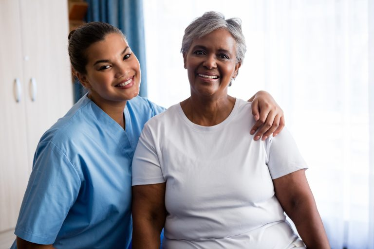 Portrait of young nurse with senior patient in nursing home